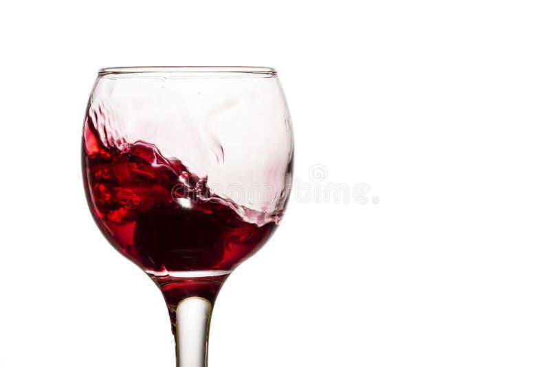 Uva al fondo di un vetro sotto un vino rosso di spruzzatura fotografia stock libera da diritti
