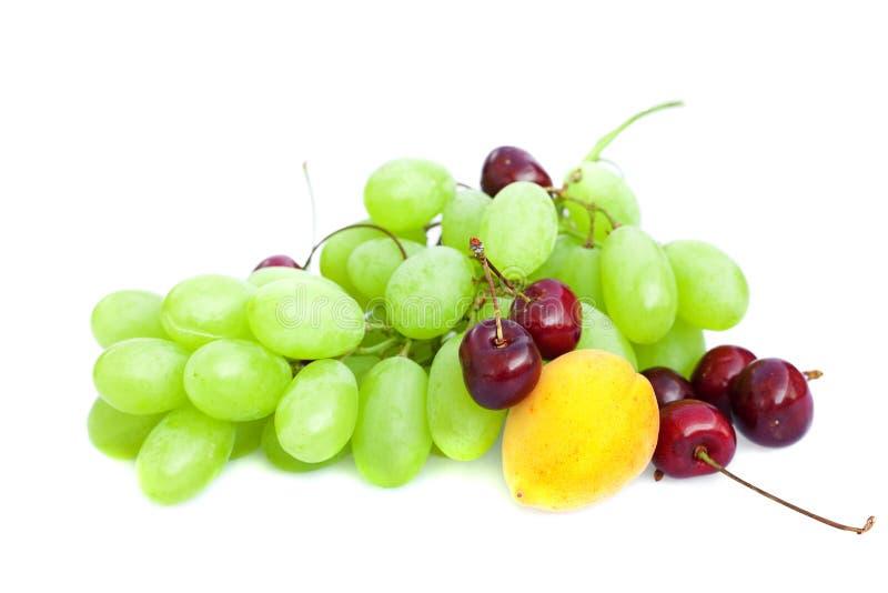 Uva, ciliege ed albicocche isolate su bianco fotografia stock libera da diritti