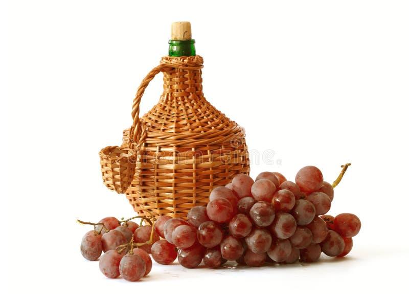 Uva con la botella de vino fotografía de archivo