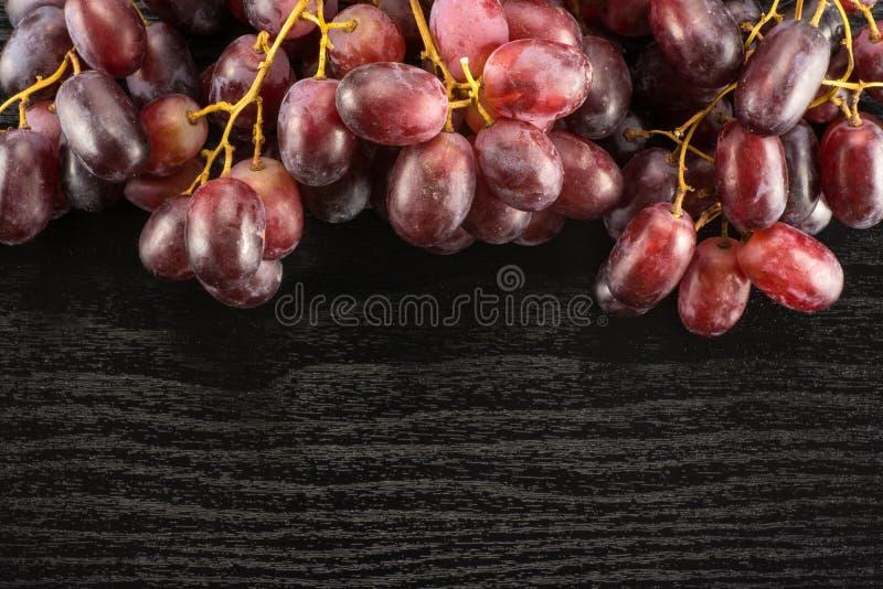 Uva cruda fresca del vino rosso su legno nero fotografia stock