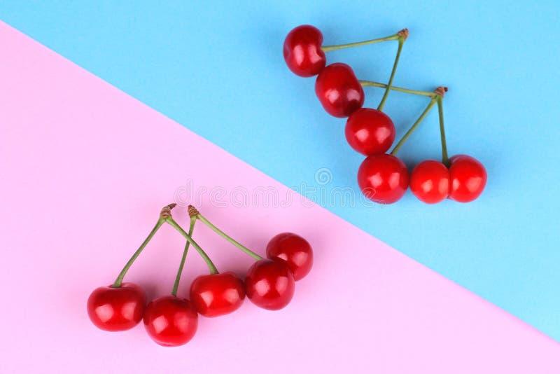 Uva delle ciliege rosse, mature, fresche su un fondo di carta blu e rosa Vista superiore fotografie stock