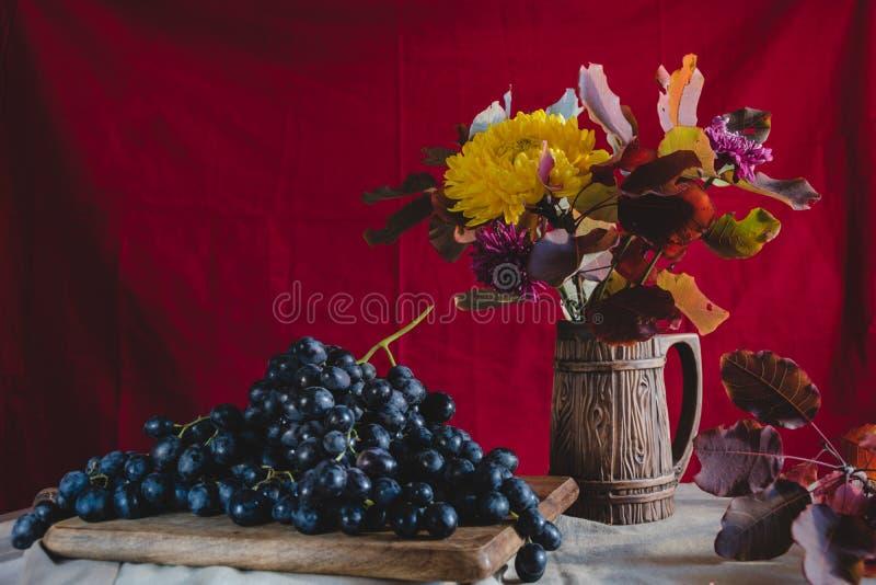 Uva di natura morta di autunno e fiori di autunno immagine stock