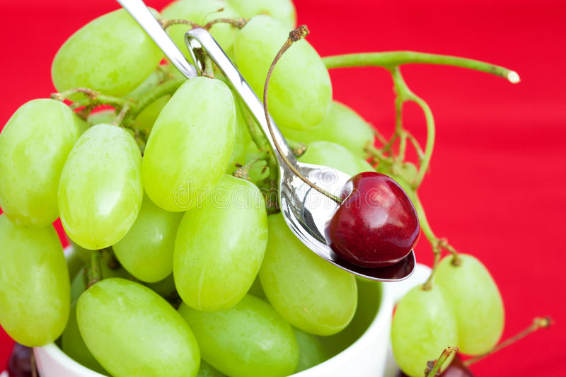 Uva e ciliege in un cucchiaio fotografia stock