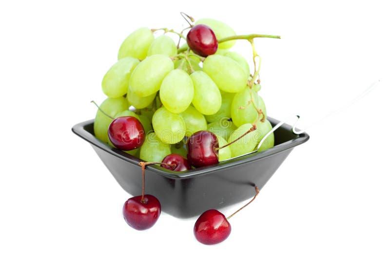 Uva e ciliege in una ciotola isolata su bianco immagine stock libera da diritti
