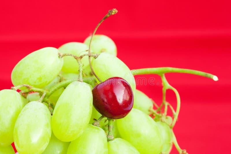 Uva e ciliegia su una priorità bassa rossa immagini stock