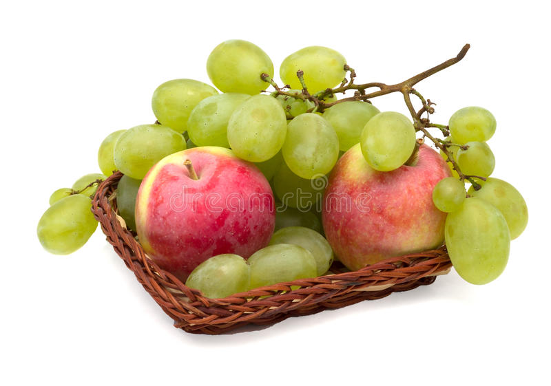 Uva e mele in un canestro di vimini fotografie stock