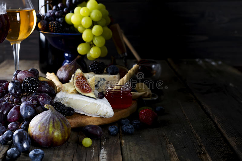 Uva, formaggio, fichi e miele con i vetri di vino bianco fotografia stock libera da diritti