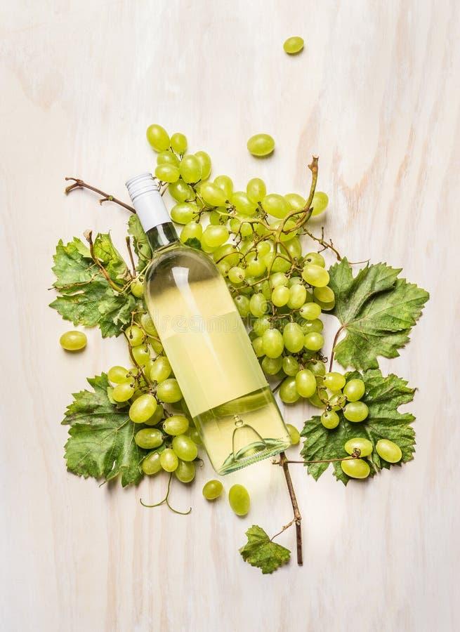 Uva fresca sul ramo con le foglie e la bottiglia di vino bianco su fondo di legno bianco, vista superiore fotografie stock libere da diritti