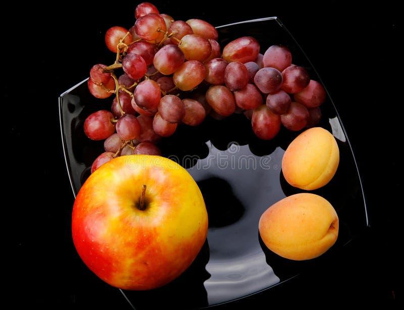 Uva, maçã e appricots Ainda vida no preto foto de stock royalty free