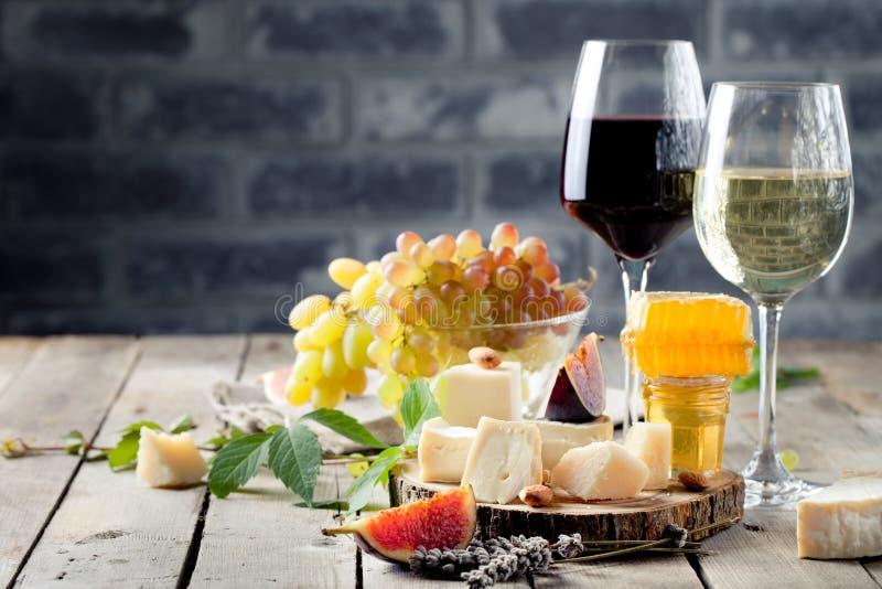 A uva, o queijo, os figos e o mel com uns vidros wine fotos de stock