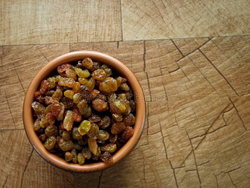 Uva passa, in un piatto marrone dell'argilla sulla tavola fotografia stock