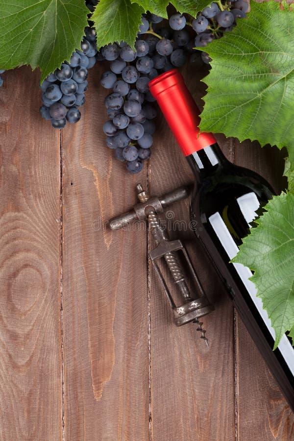 Uva roja, botella de vino y sacacorchos fotos de archivo