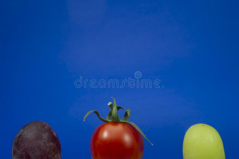Uva rossa e verde del pomodoro ciliegia su un blu fotografia stock