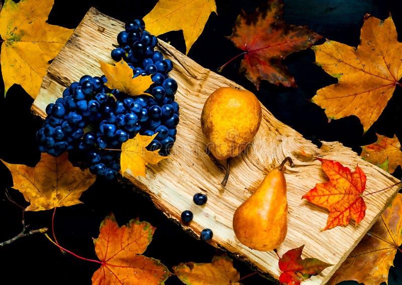 Uva scura e pere gialle su una struttura di legno naturale su un fondo di belle foglie arancio, vista superiore, spazio della cop fotografie stock libere da diritti