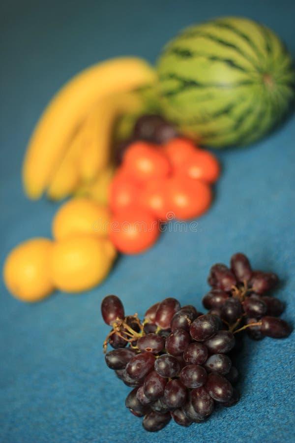 Uva senza semi rossa organica fresca sul fondo di frutti e del blu fotografia stock