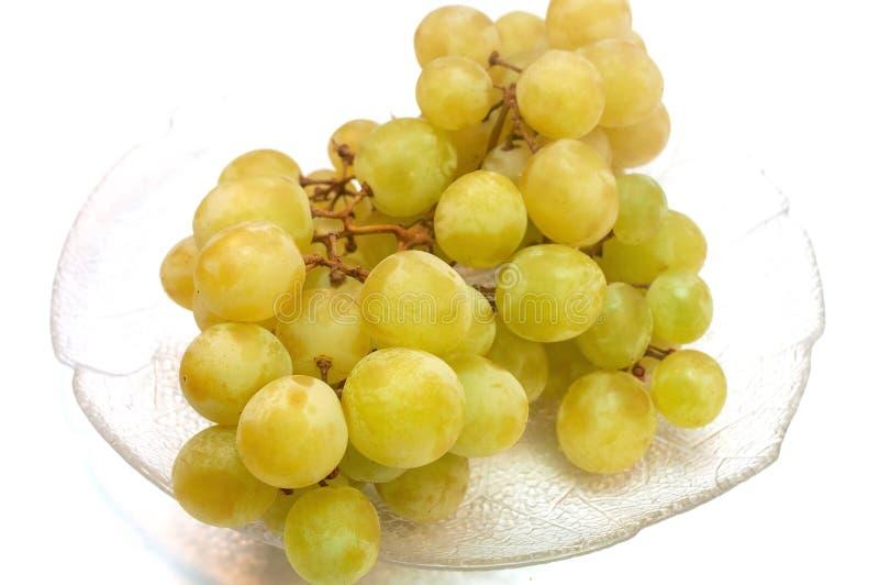 Uva senza semi in un piatto isolato su bianco fotografie stock