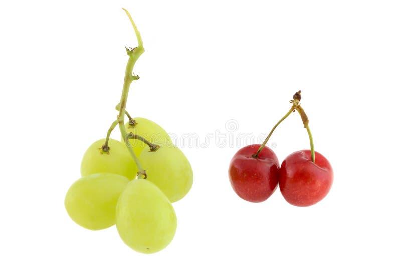 Uva succosa e ciliege mature Frutti stagionali Ha isolato un fondo bianco immagine stock
