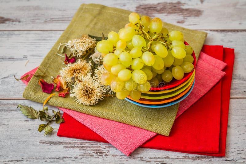 Uva verde sui piatti variopinti e sui tovaglioli fotografia stock