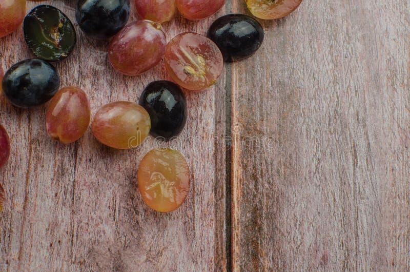 Uvas azules con la consumición sana de la hoja verde, aislado imagenes de archivo
