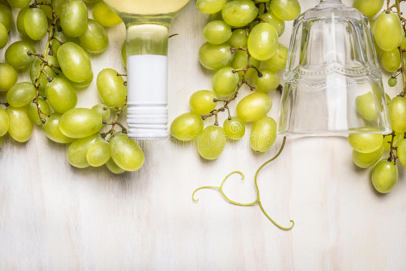 Uvas brilhantes com uma garrafa do vinho branco e do vidro em rústico um fundo de madeira branco foto de stock royalty free