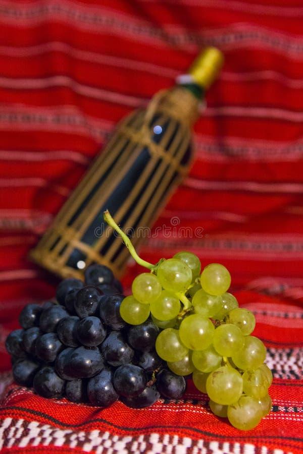 Uvas de garrafa de vinho, vermelhas e brancas em um tradicional fotografia de stock