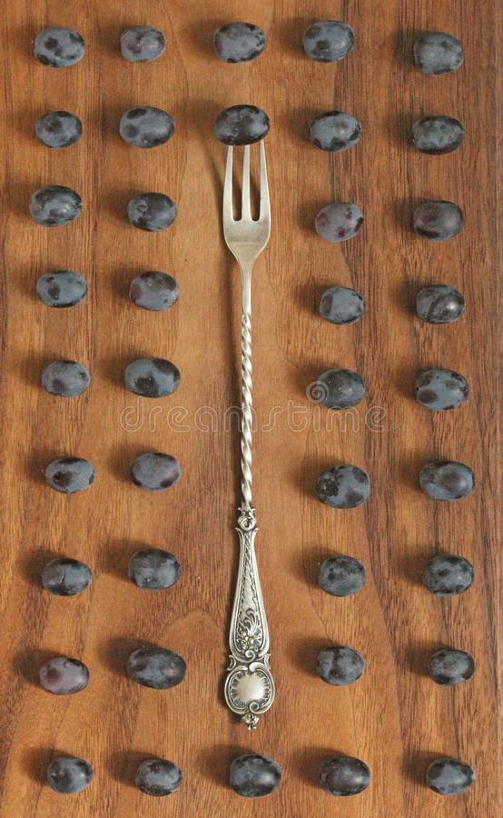Uvas Diseño conceptual Las uvas se arreglan en filas alrededor de la bifurcación del vintage, en un fondo de madera Diseño inusua imagen de archivo libre de regalías