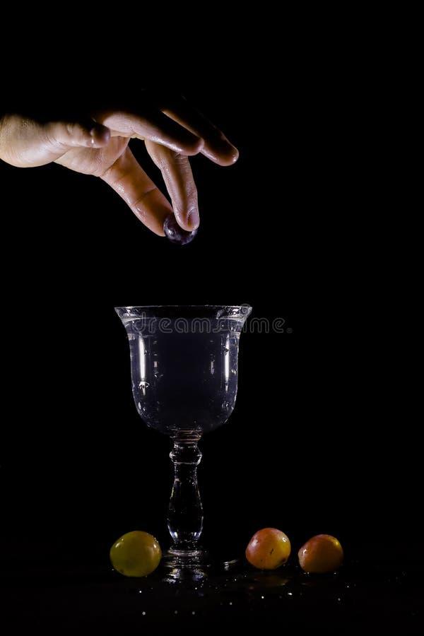 Uvas do lance em um respingo de vidro ?gua-enchido foto de stock royalty free