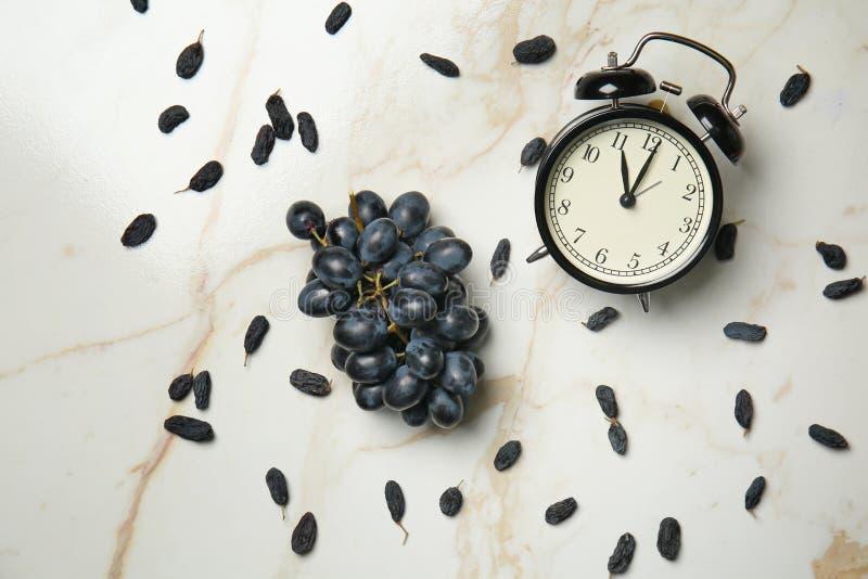 Uvas dulces maduras con las pasas y el despertador en la tabla ligera foto de archivo libre de regalías