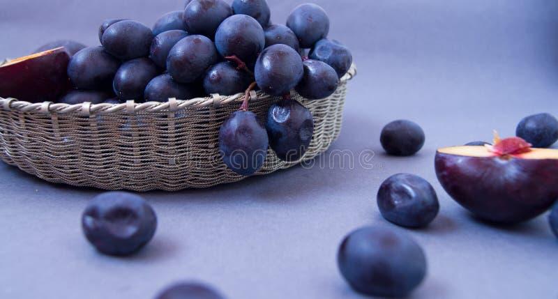Uvas e ameixas em uma bacia de prata em um fundo escuro fotos de stock royalty free