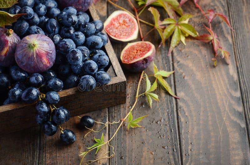 Uvas e higos negros frescos en bandeja de madera oscura en la tabla de madera foto de archivo