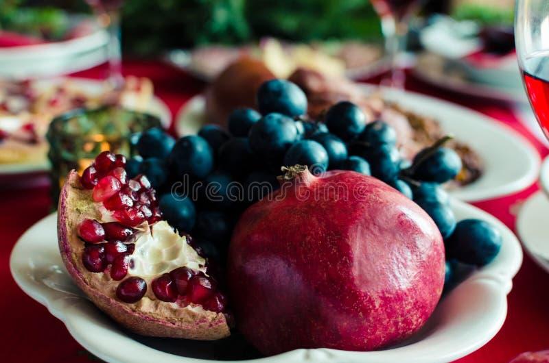 Uvas e romã tradicionais do fruto do símbolo na tabela de jantar da celebração do ano novo Ajuste de lugar festivo para o feriado fotos de stock royalty free