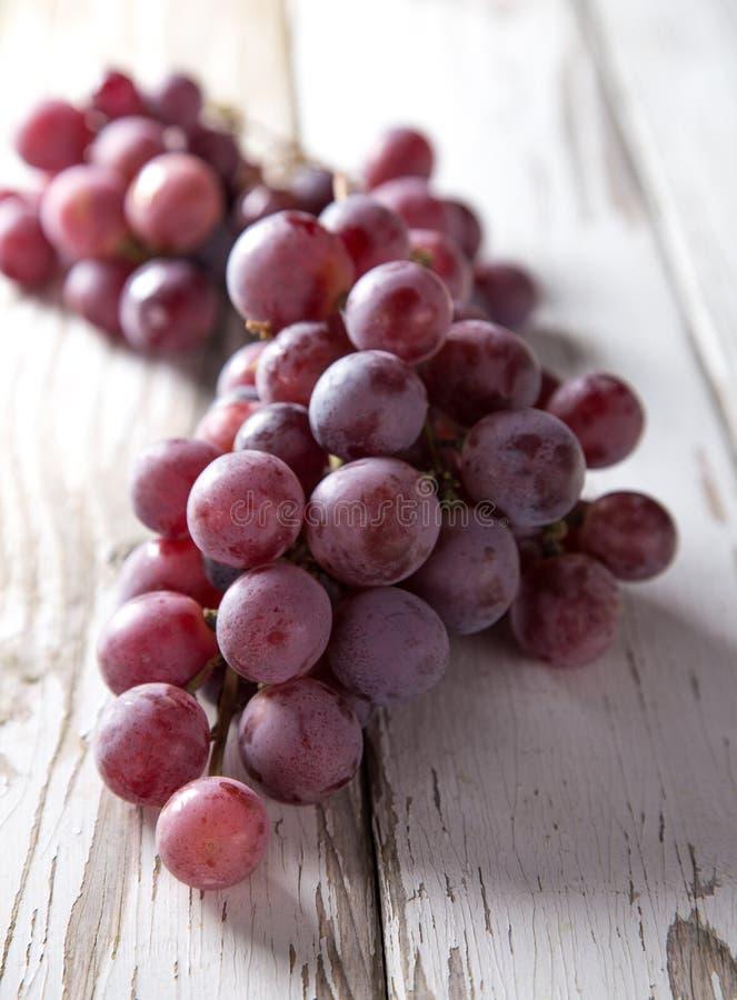 Uvas en la tabla de madera imagen de archivo