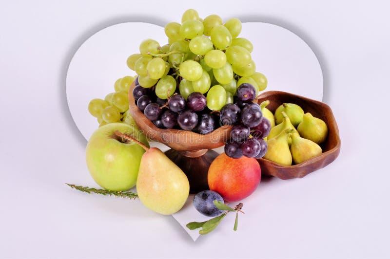 Uvas ligeras y oscuras en un cuenco de madera con un ciruelo y los higos de la pera de la manzana en un fondo blanco Todavía de l fotografía de archivo