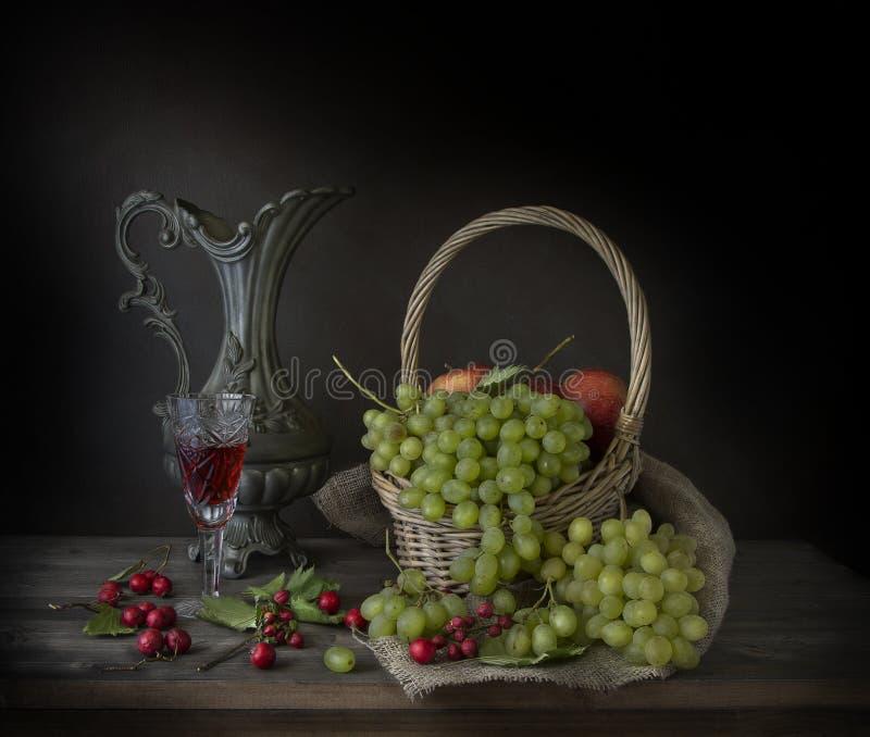 Uvas maduras, un vidrio de vino y bayas del otoño en la tabla foto de archivo