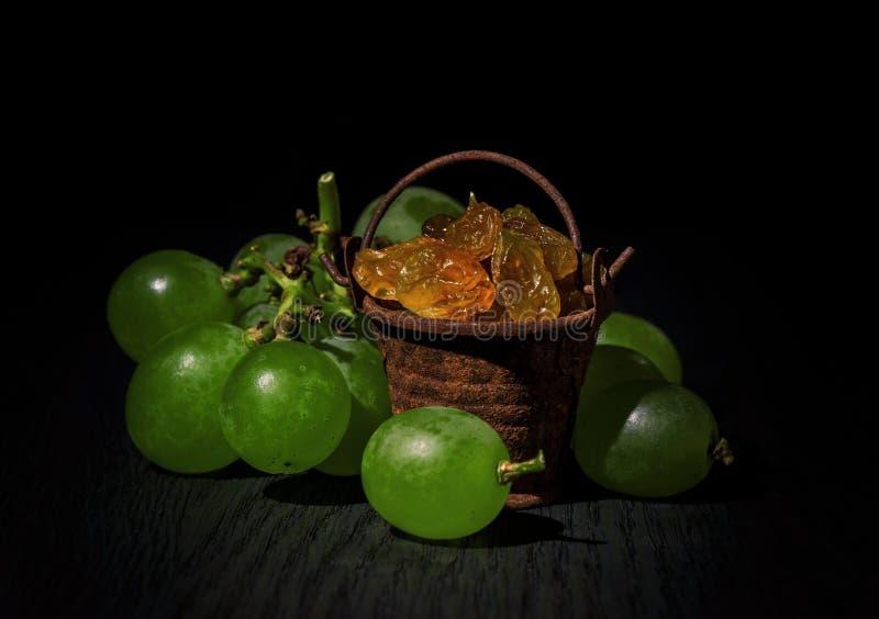 Uvas, pasas en un cubo viejo, en un fondo oscuro foto de archivo libre de regalías