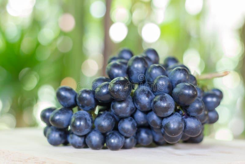 Uvas pretas em de madeira fotos de stock