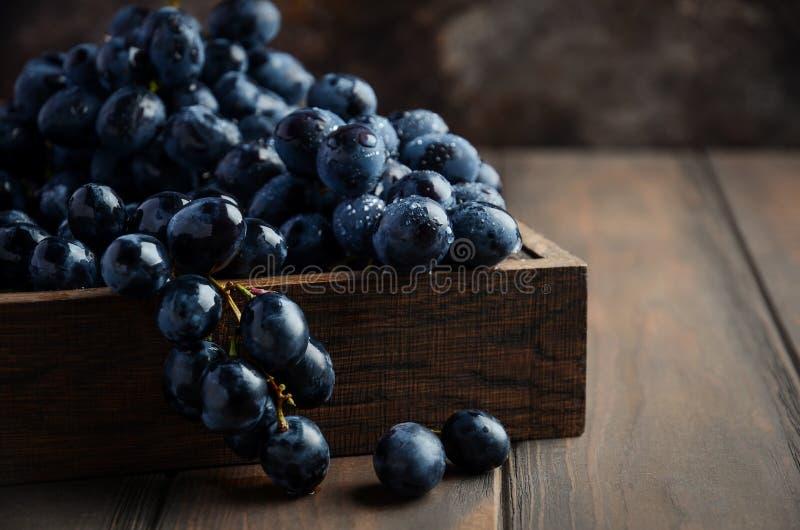 Uvas pretas frescas na bandeja de madeira escura na tabela de madeira foto de stock