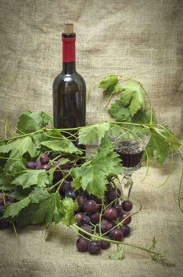 Uvas rojas dulces con la botella de vino rojo imagenes de archivo