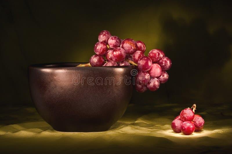 Uvas rojas en tazón de fuente negro fotos de archivo