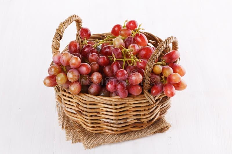 Uvas rojas en una cesta tejida sobre el fondo blanco imagen de archivo