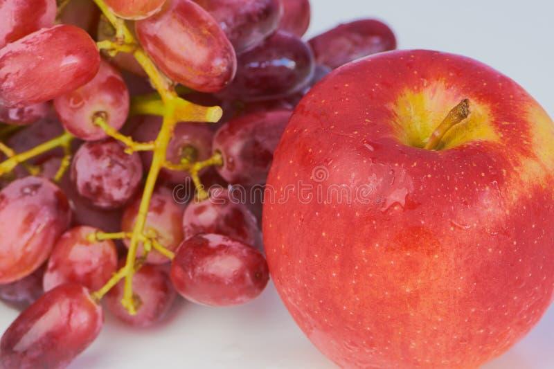 Uvas rojas y manzana roja contra el fondo blanco foto de archivo