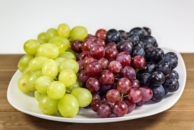 Uvas sin semillas negras, rojas, verdes en un cuenco blanco profundo imágenes de archivo libres de regalías