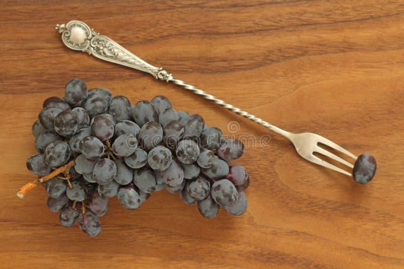 Uvas Um grupo de mentiras escuras, pretas das uvas em um close-up da placa de madeira e de uma forquilha do vintage imagem de stock royalty free
