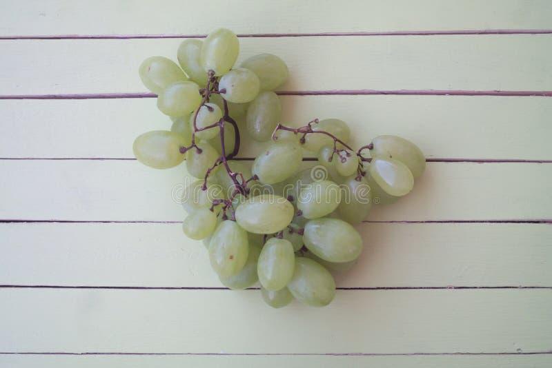 Uvas verdes en la madera verde desde arriba foto de archivo