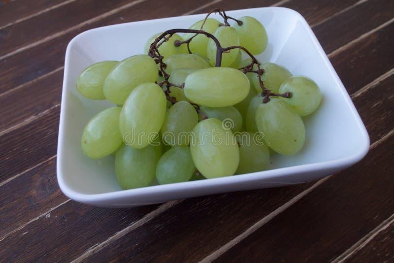 Uvas verdes en un cuenco blanco en la madera foto de archivo