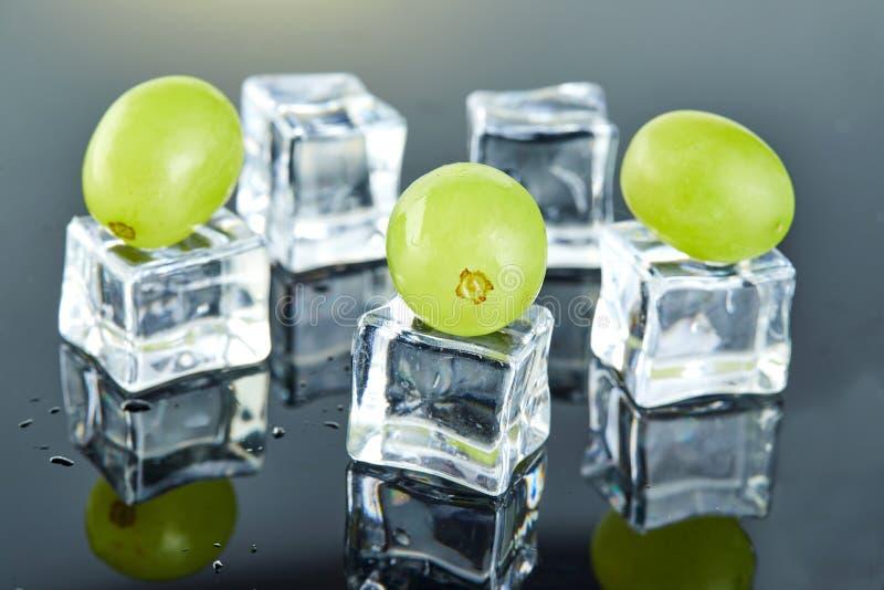 Uvas verdes frescas con descensos del agua y cubos de hielo en fondo gris imágenes de archivo libres de regalías