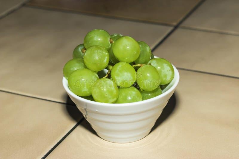 Uvas verdes na bacia branca fotos de stock royalty free