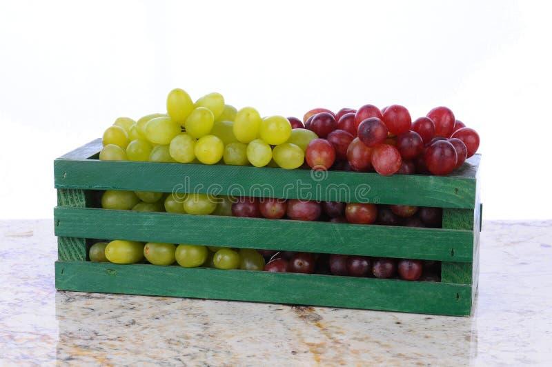 Uvas vermelhas e verdes na caixa de madeira foto de stock