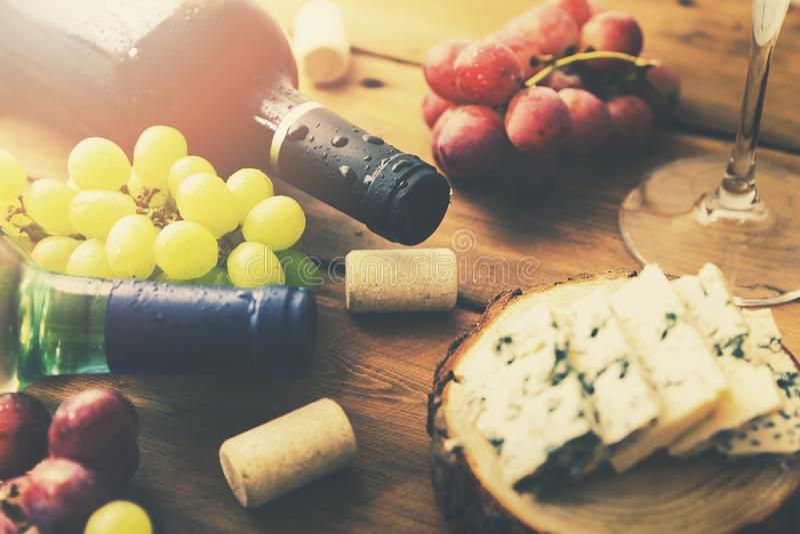 Uvas y queso de las botellas de vino en la tabla de madera vieja fotografía de archivo libre de regalías