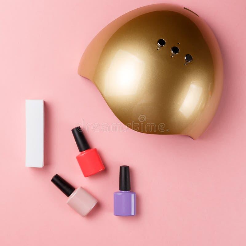 UVlampenlichter f?r N?gel und Satz kosmetische Werkzeuge f?r Manik?re und Pedik?re auf Pastellhintergrund stockfoto
